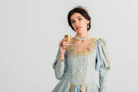 Photo pour Attractive queen with crown holding cup isolated on grey - image libre de droit