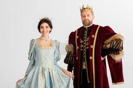 smiling queen and king with crowns isolated on grey