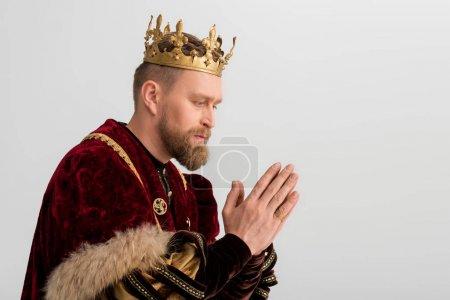 Photo pour Vue latérale du roi avec couronne priant isolé sur gris - image libre de droit
