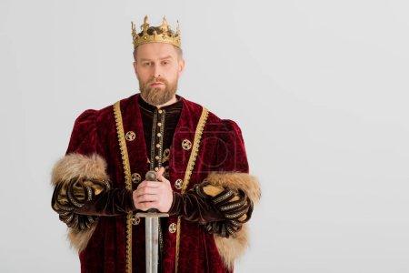 Photo pour Roi sérieux avec couronne tenant épée isolé sur gris - image libre de droit