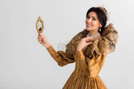 Photo pour Smiling queen with crown holding mirror isolated on grey - image libre de droit