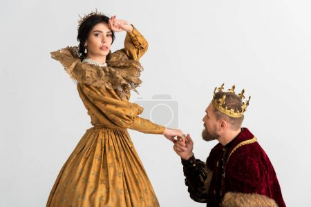 Photo pour King with crown holding hand of shocked queen isolated on grey - image libre de droit
