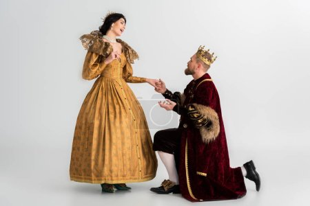 Photo pour King with crown bending on knee and holding hand of shocked queen on grey background - image libre de droit