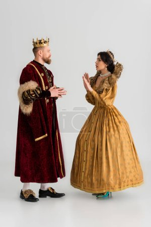 Photo pour Side view of shocked queen showing no gesture to king with crown on grey background - image libre de droit