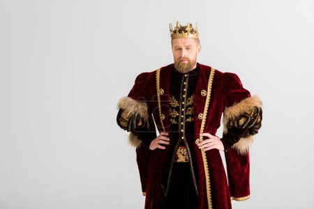 Photo for Handsome king with crown with hands on hips looking at camera isolated on grey - Royalty Free Image