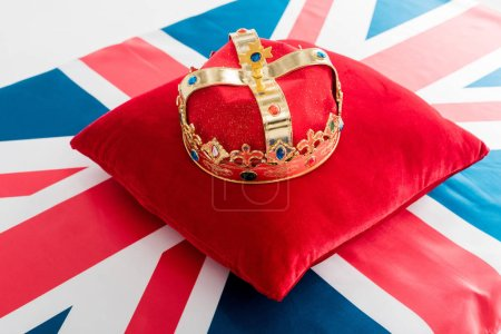 golden crown on red pillow and british flag