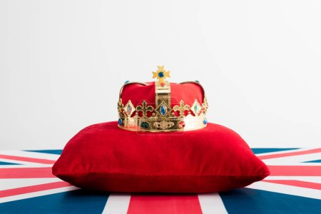 golden crown on pillow and british flag isolated on white