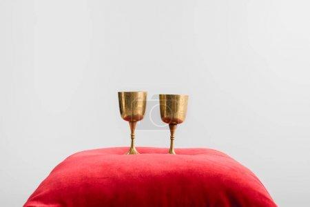 tasses dorées sur oreiller rouge isolé sur blanc