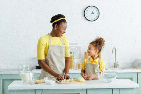 happy african american mother and daughter sculpting raw dumplings in kitchen