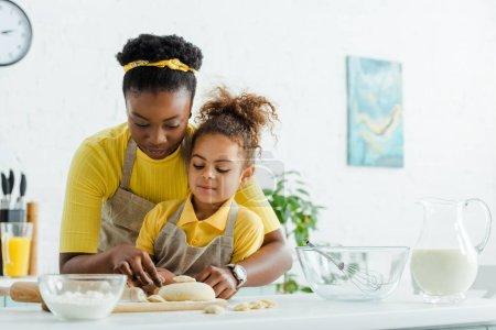 Photo pour Mère africaine américaine près d'adorables chevreaux sculptant des boulettes dans la cuisine - image libre de droit