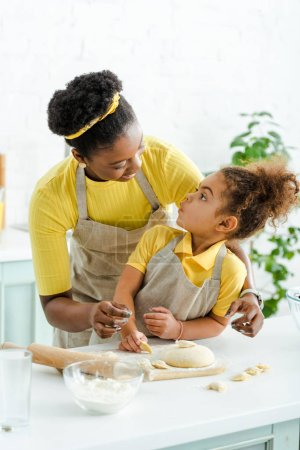 Photo pour Happy african american mother looking at adorable kid and sculpting dumplings in kitchen - image libre de droit