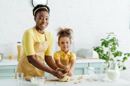 Photo pour African american mother near happy kid sculpting dumplings in kitchen - image libre de droit