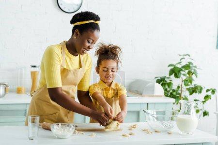 Photo pour Joyeuse mère africaine américaine et joyeuse enfant sculptant des boulettes dans la cuisine - image libre de droit