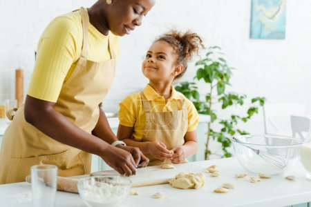 Photo pour Happy African american kid looking at mother sculpting dumplings in kitchen - image libre de droit