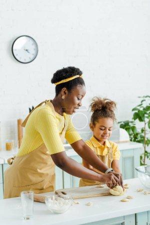 Photo pour Joyeuse mère africaine américaine et joyeuse enfant sculptant des boulettes crues dans la cuisine - image libre de droit