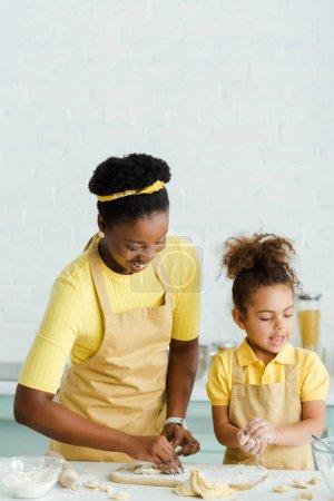 Photo pour Joyeuse mère africaine américaine et joyeuse fille en tablier sculptant dumplings crus dans la cuisine - image libre de droit