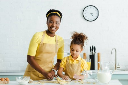 Photo pour Happy african american mother and cute daughter in apron sculpting raw dumplings in kitchen - image libre de droit