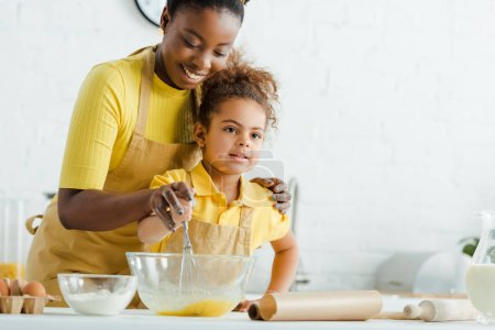 Photo for Cute african american kid and cheerful mother holding whisk near bowl while cooking in kitchen - Royalty Free Image