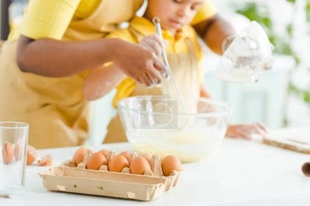 Photo for Selective focus of eggs near african american kid and mother mixing ingredients in bowl - Royalty Free Image
