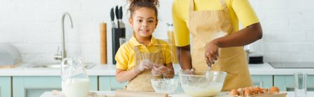 panoramic shot of african american mother holding whisk near bowl and cute daughter