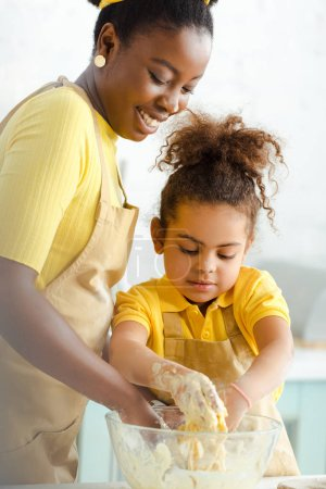 Photo for Happy african american mother and adorable daughter kneading dough - Royalty Free Image