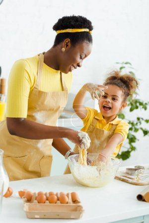 happy african american mother kneading dough near cheerful daughter