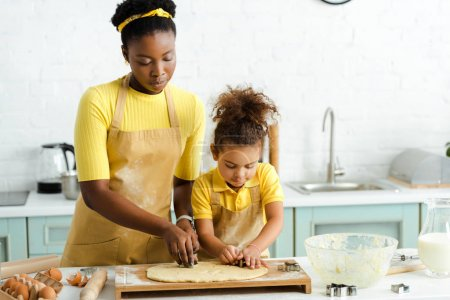 Photo for Adorable african american kid and mother holding cookie cutters near raw dough - Royalty Free Image