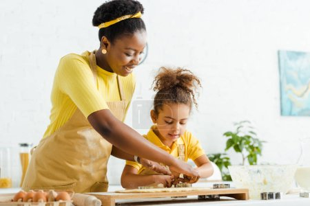 Photo pour Happy african american mother and daughter holding cookie cutters near dough - image libre de droit