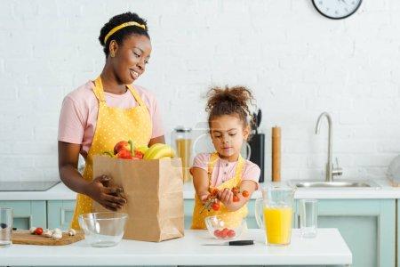 attraktive afrikanisch-amerikanische Mutter schaut Tochter mit Kirschtomaten an