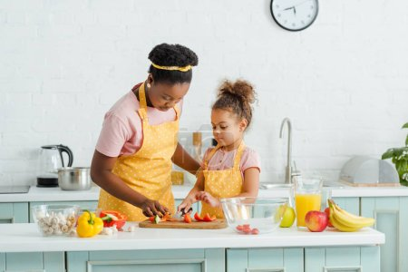 Foto de Madre afroamericana e hija cortando pimiento morrón en tabla de cortar - Imagen libre de derechos