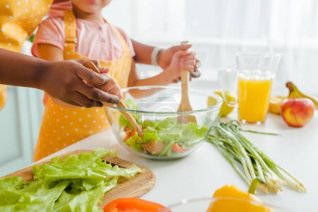 Photo for Cropped view of african american mother and daughter mixing fresh salad - Royalty Free Image