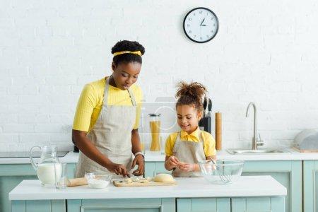 Photo pour Mère et fille d'origine africaine sculptant des dumplings près d'une cruche avec du lait dans la cuisine - image libre de droit