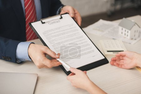 Photo for Cropped view of agent giving pen to client and holding clipboard with contract lettering - Royalty Free Image