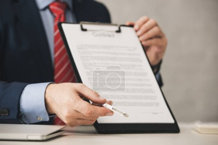 Photo for Cropped view of agent holding clipboard with contract lettering and pen - Royalty Free Image