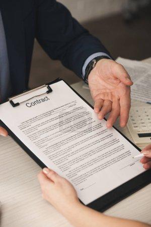 vue recadrée de l'agent pointant avec la main au presse-papiers avec lettrage contrat près de la femme avec stylo