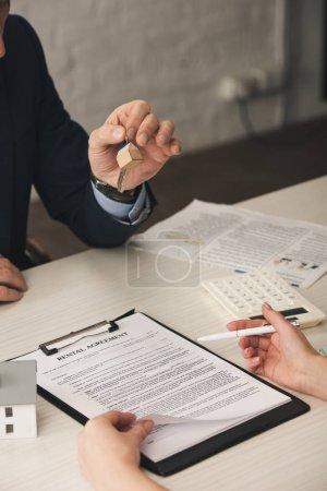 Photo pour Vue en coupe d'une femme tenant un stylo près du presse-pantalon avec contrat de location lettres et courtier avec clés - image libre de droit