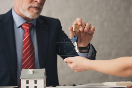 Photo pour Vue en coupe d'un agent remettant des clés à un client près d'une maison de carton - image libre de droit