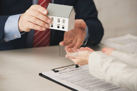 Photo for Cropped view of agent giving house model to woman with cupped hands - Royalty Free Image