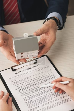 Photo pour Top view of agent holding house model near woman with pen in hand and rental agreement - image libre de droit