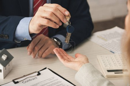 Photo for Cropped view of realtor giving keys to woman with cupped hand near contract - Royalty Free Image