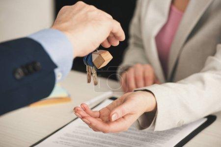 Photo pour Focalisation sélective d'un courtier immobilier donnant des clés à une femme au pouvoir - image libre de droit