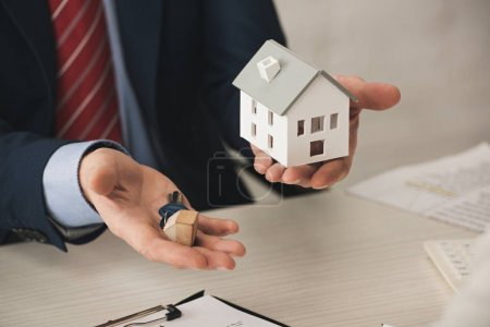 cropped view of realtor holding keys and carton house model in office