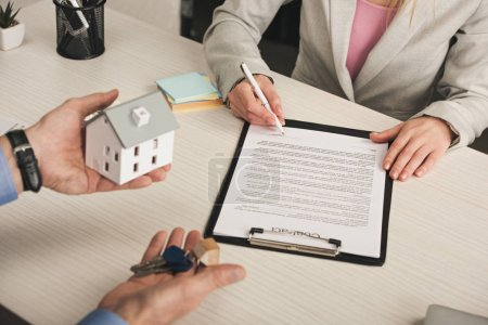 Photo pour Crochet vue de l'homme tenant les clés et modèle de maison près de la femme signant le contrat - image libre de droit