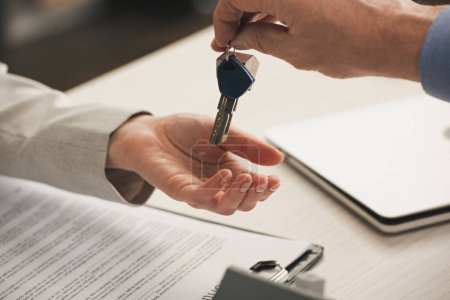 Photo for Cropped view of man giving keys to client - Royalty Free Image