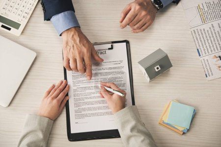 Photo pour Top view of agent pointing with finger at clipboard with contract lettering near woman - image libre de droit