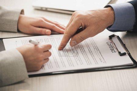 Photo pour Crochet de l'agent immobilier pointant avec le doigt au planche à reliure avec les lettres de contrat près de la femme - image libre de droit