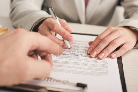 Photo for Selective focus of realtor pointing with finger at clipboard with lettering near client - Royalty Free Image
