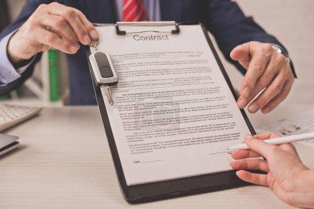 Photo pour Vue en coupe de l'agent tenant la planche à papiers avec le lettrage du contrat et la clé de voiture près de la femme - image libre de droit