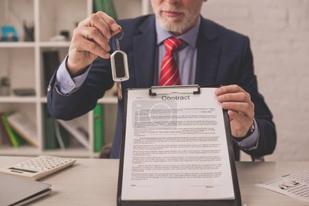 Photo for Cropped view of bearded agent holding clipboard with contract lettering and car key - Royalty Free Image