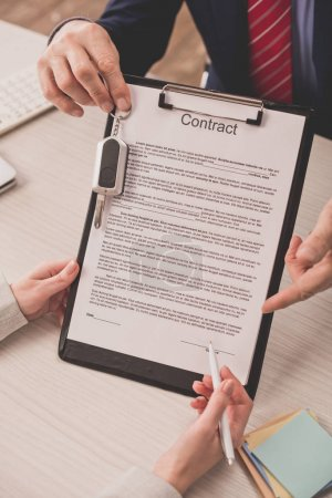 cropped view of agent pointing with finger at clipboard with contract lettering and car key near client
